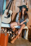 Attractive bohemian woman sitting on a bench in wooden house, guitar. Standing near royalty free stock images