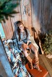 Attractive bohemian woman sitting on a bench in wooden house, guitar stock photography