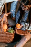 Attractive bohemian woman sitting on a floor with basket of fruits. And holding orange royalty free stock photos