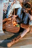 Attractive bohemian woman sitting on a floor and looking at basket royalty free stock photography
