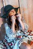 Attractive bohemian woman sitting at home. And playing harmonica stock photo