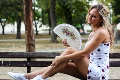Attractive and Bored Blonde Girl With Curly Hair Sitting on the. Bench in a Park and Cooling Herself Down With a Paper Fan Stock Photography