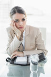 Attractive bored businesswoman looking at camera while sitting at her desk Stock Photo