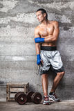 Attractive boxer man standing on the wall and looking aside. Portrait of attractive boxer man standing on the wall and looking aside Royalty Free Stock Images