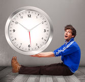 Attractive boy holding a huge clock Stock Photography