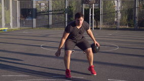 Attractive boy playing with ball at the open air. Adult caucasian man dribbling ball and running to the basketball hoop on the court at the open air. Male trains stock video footage
