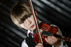 Attractive boy playing violin, studio shooting Royalty Free Stock Image