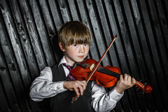 Attractive boy playing violin, studio shooting Stock Images