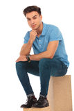 Attractive boy seated on box Royalty Free Stock Images