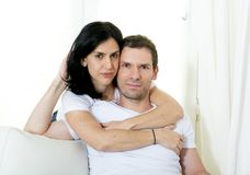Attractive Brazilian couple with standing woman hugging his husband sitting in living room couch smiling happy in love concept Stock Photography