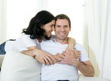 Attractive Brazilian couple with standing woman hugging his husband sitting in living room couch smiling happy in love concept Stock Photos