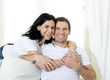 Attractive Brazilian couple with standing woman hugging his husband sitting in living room couch smiling happy in love concept Stock Images