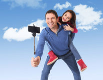 Attractive Brazilian father carrying cute young daughter on his back having fun smiling happy taking selfie photo with mobile phon Stock Images