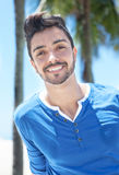 Attractive brazilian guy with palms and blue sky in the background. Attractive brazilian guy laughing at camera outside with palms and blue sky in the background Stock Photography