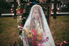 Attractive bride in bohemian white dress and veil holding. Wedding bouquet stock photos