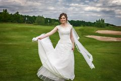 Attractive bride dancing on green golf course. Attractive young bride in a modern white dress dancing on a green golf course . Concept of fashion modern bride Royalty Free Stock Image