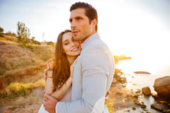 Attractive bride and groom getting married by the beach. At sunset Stock Photos