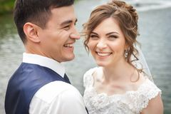 Attractive bride and groom smiling near the pond Royalty Free Stock Photos