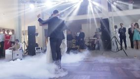 Attractive bride and handsome groom are dancing their first dance in the luxury restaurant hall.