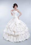 Attractive bride model girl wearing in wedding dress with volumi. Nous skirt, studio photo Stock Photos