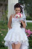 Attractive bride in the park. Bride posing looking at camera smiling Royalty Free Stock Image