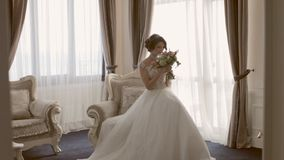 Attractive bride sitting in the chair with the bouquet in hands stock footage