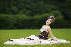 Attractive bride sitting on green field Stock Photo