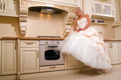Attractive bride sitting in the kitchen Royalty Free Stock Photo