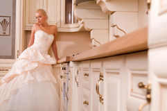 Attractive bride sitting in the kitchen Royalty Free Stock Image