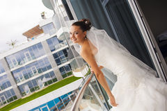 Attractive bride is standing on the balcony. Royalty Free Stock Image