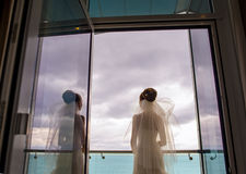 The attractive bride is standing on the balcony. Royalty Free Stock Photo