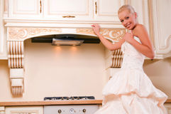 Attractive bride stands in the kitchen Stock Photo