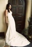 Attractive bride wearing beautiful dress. Beautiful attractive brunette bride wearing gorgeous wedding dress standing next to arch doorway Stock Photography
