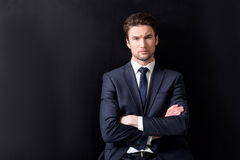 Attractive bristled guy is sitting against dark wall Royalty Free Stock Photos