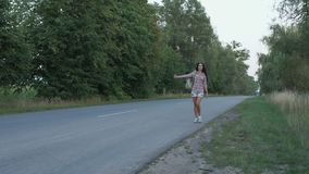 Beautiful woman catches the hitch-hiking car on the road. Attractive brown-haired woman walks over the road. Beautiful lady holding her backpack holds thumb-up stock footage