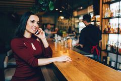 Attractive brunete girl sitting in the club near bar stand and talking on the phone. She is smiling. Barman stands not stock image