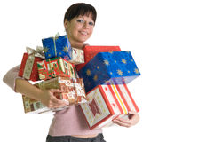 Attractive brunette with armful of X-mas presents. Young brunette with armful of Christmas presents isolated over white Royalty Free Stock Photo