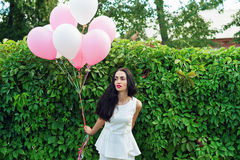 Attractive brunette with balloons near the green hedgerow Stock Image