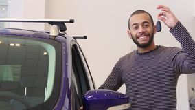 Man stands near the purple crossover at the showroom. Attractive brunette bearded man standing near the purple crossover at the dealership. Young african Royalty Free Stock Photo