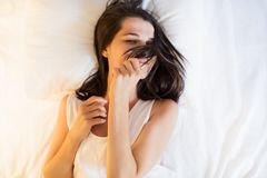 Attractive brunette beautiful young woman on the white bed in wh. Ite t-shirt, playing with hair and smiling Royalty Free Stock Photos