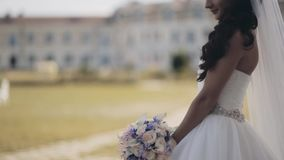 Attractive brunette bride standing in nature wearing the wedding dress. Beautiful woman holds bouquet, waits ceremony. stock video footage