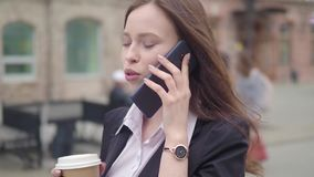 Attractive brunette Business Woman Using Smartphone in the City. Pretty Young Business Woman Talking by Phone and. Drinking coffee stock video