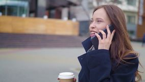 Attractive brunette Business Woman Using Smartphone in the City. Pretty Young Business Woman Talking by Phone and. Drinking coffee stock video footage