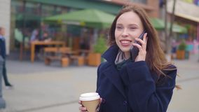 Attractive brunette Business Woman Using Smartphone in the City. Pretty Young Business Woman Talking by Phone and. Drinking coffee stock footage