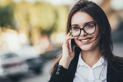 Attractive brunette businesswoman talking on mobile phone with client. Close up.  stock images