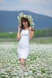 Attractive brunette in chamomile wreath Stock Photo