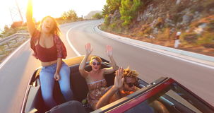 Attractive brunette dancing while sitting on hood of convertible stock footage