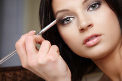 Attractive brunette doing make-up. Stock Photos