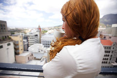 Attractive brunette drinking coffee in balcony Stock Image