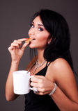 Attractive brunette drinking tea with cookies. Attractive playful brunette drinking tea with cookies Stock Images